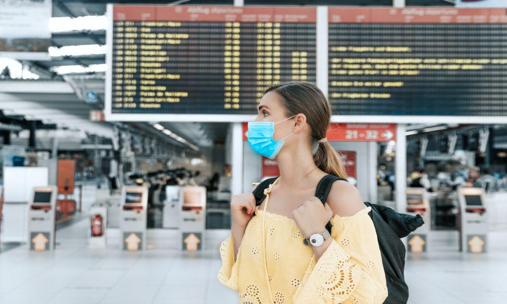 Frau mit Mund-Nasen-Maske steht am Flughafen
