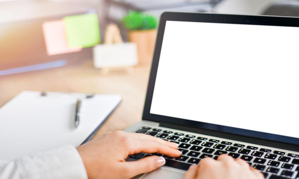 Eine Person tippt auf einem Laptop.