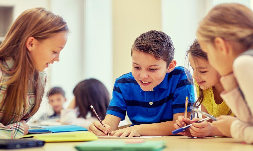 Vier Kinder vervollständigen zusammen ein Dokument