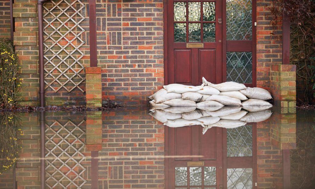 Eine Straße ist überflutet und Sandsäcke schützen eine Tür.